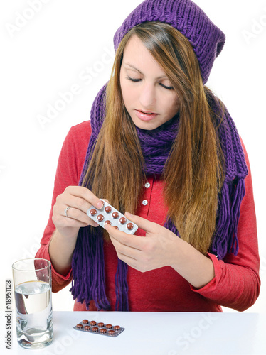 cute girl taking medicine against a white background