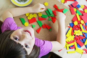 Preschool girl playing with puzzle