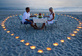 A young lovers couple share a romantic dinner with candles heart