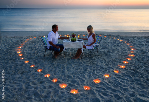A young lovers couple share a romantic dinner with candles heart - 48953744