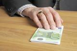 Mann schiebt Geldstapel über Tisch