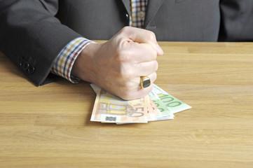 Mann haut mit Faust auf Geldscheine