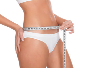 fit young woman measuring her waistline, white background