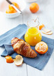 Croissant and mandarin juice on a blue napkin