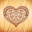 Brown ornate vector heart on wooden background