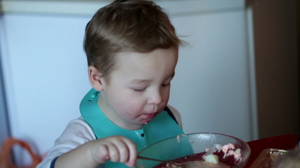 Two year old boy is eating soup from the plate. Clip one.