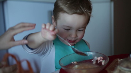 Two year old boy is eating fish soup from the plate. Clip two.