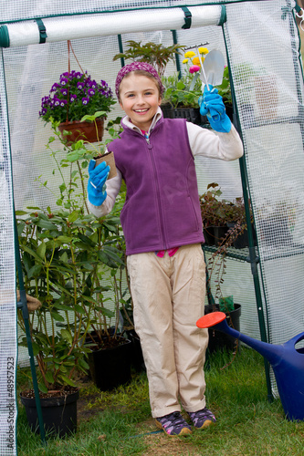 Gardening , planting - girl with seedling in green house