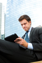 Businessman using a tablet on a bench in the city