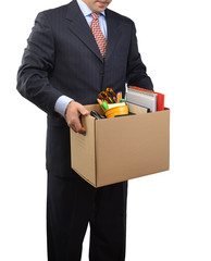Fired businessman in a suit carrying a box of personal items