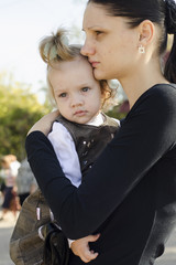 Мама держит на руках ребенка в людном месте