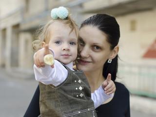 Мама держит на руках девочку, показывающую пальцем вперед