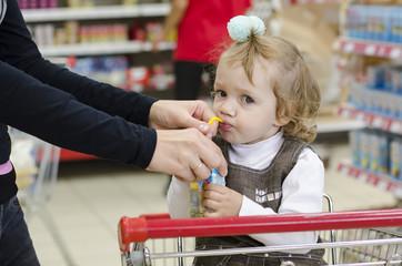 Ребенок пьет сок сидя в тележке в магазине