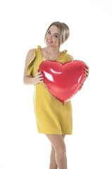 Beautiful woman holding red heart balloon over white background.