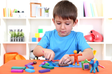 Cute little boy moulds from plasticine on table