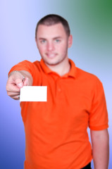 Jeune homme tenant una carte bancaire dans la main.