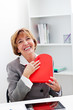 Businesswoman hugging a red heart present.