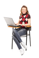 A smiling student female working on a laptop seated on a chair