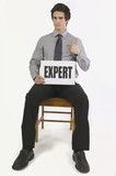 Man Holding A Sign That Says Expert