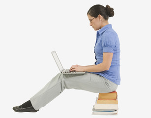 girl on laptop sitting on pile of books