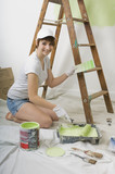 girl painting a wall green