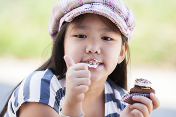Cute asian girls enjoy eating chocolate cupcake