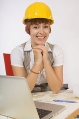 Woman Wearing Hardhat Sitting At Desk