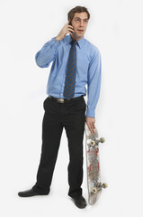 Businessman Talking On Phone And Holding Skateboard