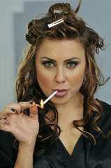 Portrait of pretty young smoking woman during makeup