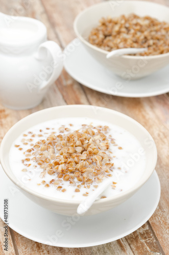 Boiled buckwheat with milk in a white bowl vertical