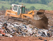 A bulldozer moving garbage on a landfill waste site
