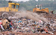 Bulldozers moving garbage on a landfill waste site