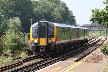 UK commuter train passing station platform