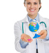 Closeup on smiling medical doctor woman holding pills and globe
