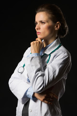 Thoughtful medical doctor woman looking on copy space