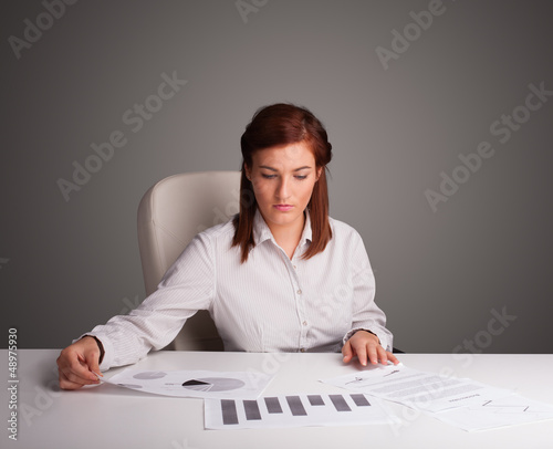 Businesswoman sitting at desk and doing paperwork