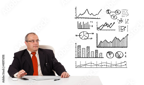 Businessman sitting at desk with diagrams and graphs