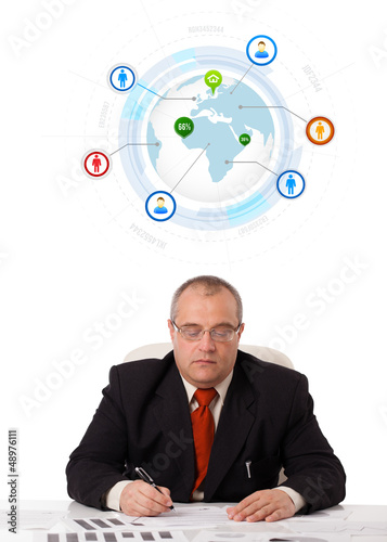 businessman sitting at desk with a globe and social icons