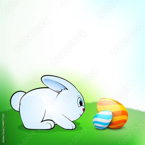 Little Easter Rabbit with beautiful painted Easter Eggs on natur
