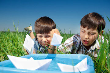 Kids playing with paper boats