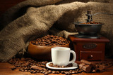 Fototapety Coffee grinder and cup of coffee on burlap background