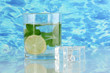 Glass of water with ice, mint and lime on sea background