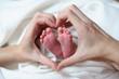 Babyfüßchen in Hand in Herzform