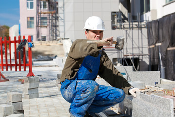 Tiler at construction site pointing at something