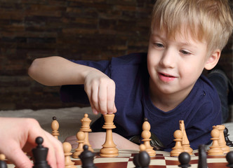 Cute blonde boy playng chess