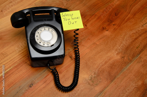 Black retro telephone with reminder note