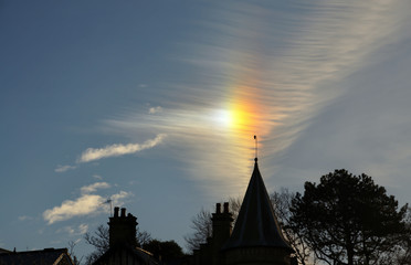 Sun dog and cirrus cloud above a church.