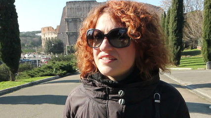 Walking happy woman in autumn colosseum park