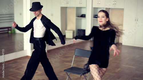 Contemporary professional dancers dancing in ballroom