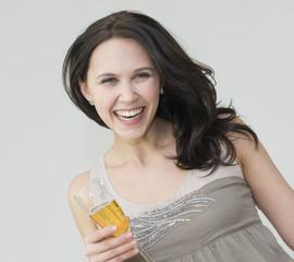 Jeune femme riant avec un verre de vin dans la main